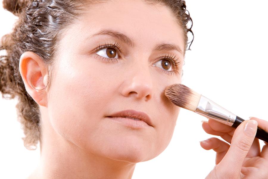 Pretty brunette applying foundation with a big brush
