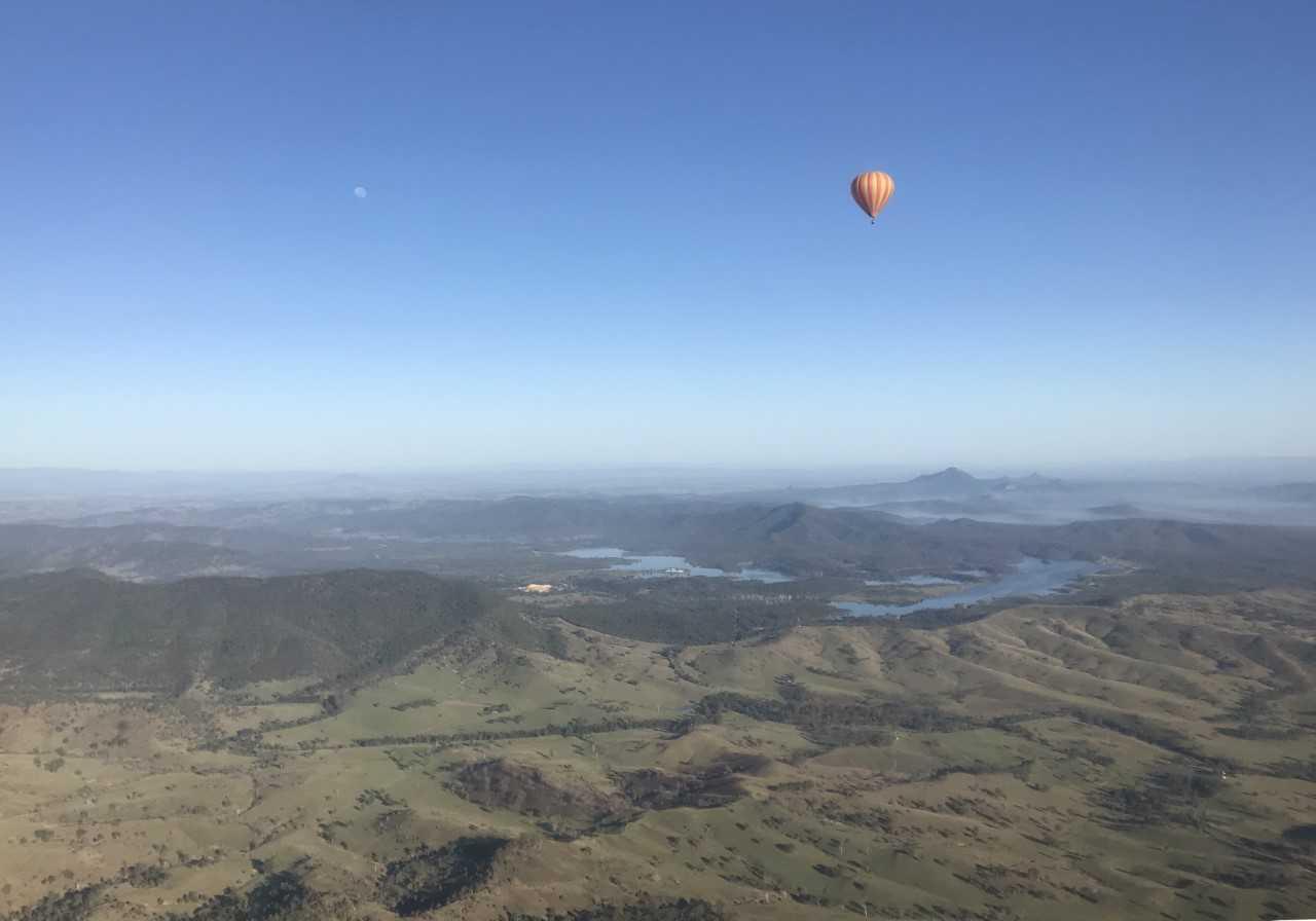 A hot air balloon floats above the hinterland surrounding Brisbane