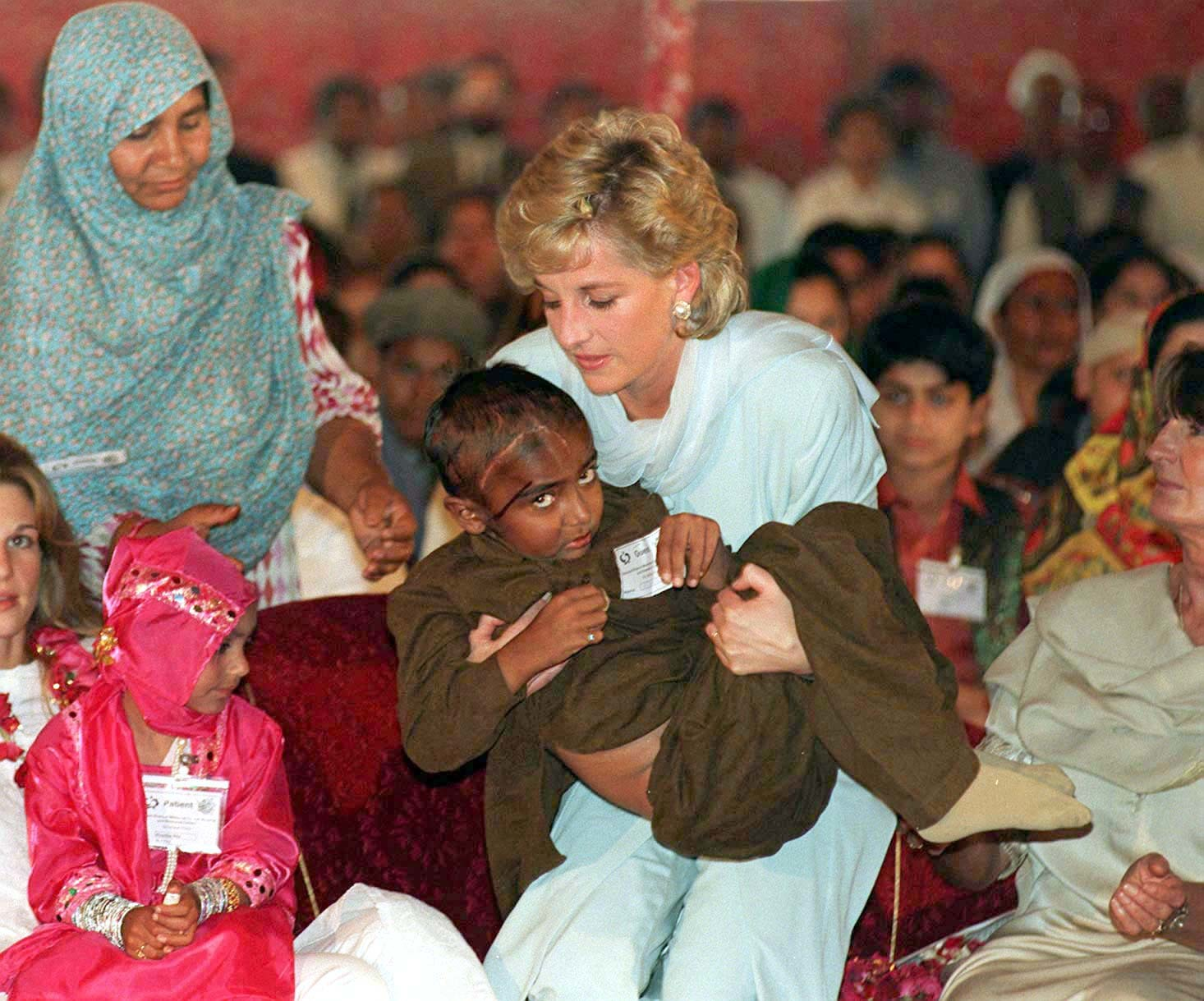 Diana cradles a sick child during a visit to Pakistan in 1996